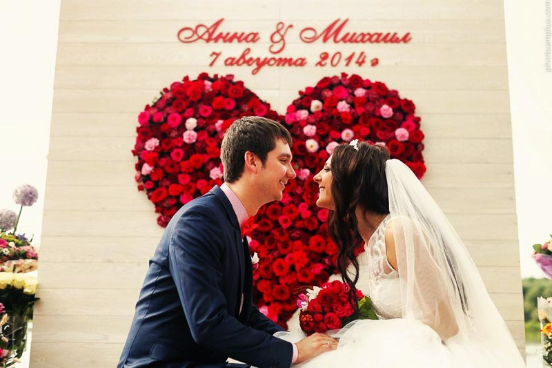изображение фотозоны с большым сердцем из искусственных цветов и именами пары: оформление свадьбы в красном цвете