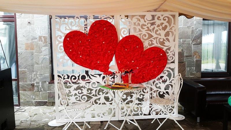 фото ажурной ширмы с большими алыми сердцами: оформление свадьбы в красном цвете